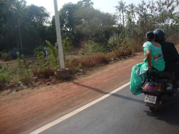 a picture taken in goa with 2 indians traveling on a motorbike