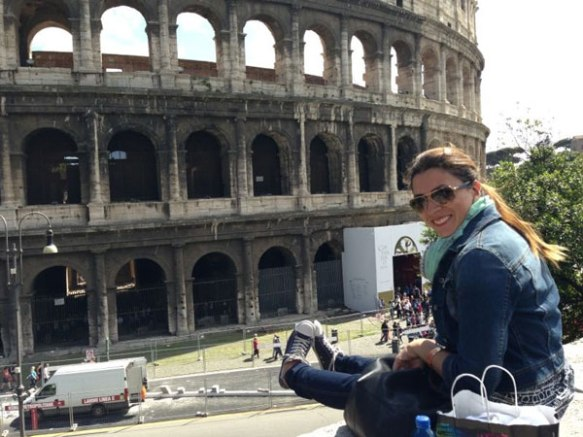 happy razan masri sitting on a cliff looking at the beautiful colloseum in jeans and converse