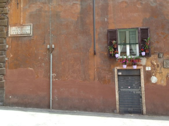 street shot with a single door and window that look super urban enriched with the art of rome