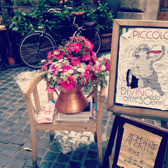 Aperitif sign with chair and a flower pot welcoming tourists at compo di fiori