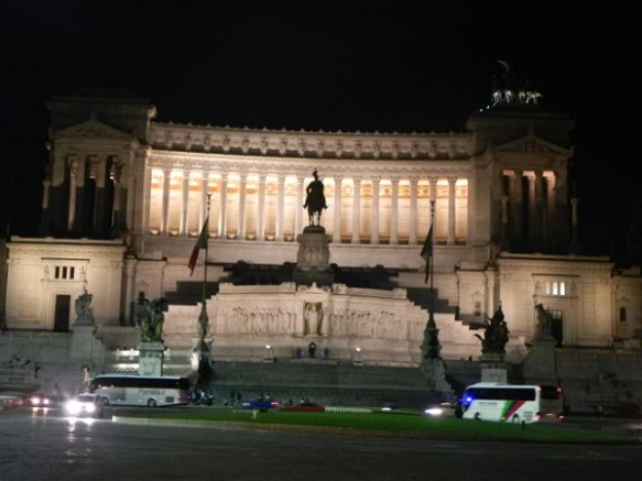 at night the lights of piazza venezia rome is superb with the man on a horse and the flags looks royal