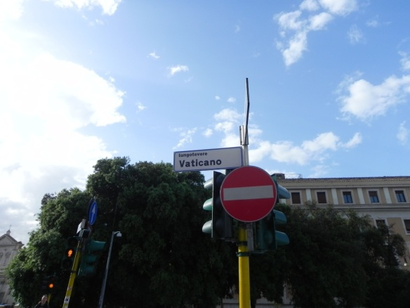 A street sign of the Vatican in Rome Italy with a no parking sign under a great blue sky