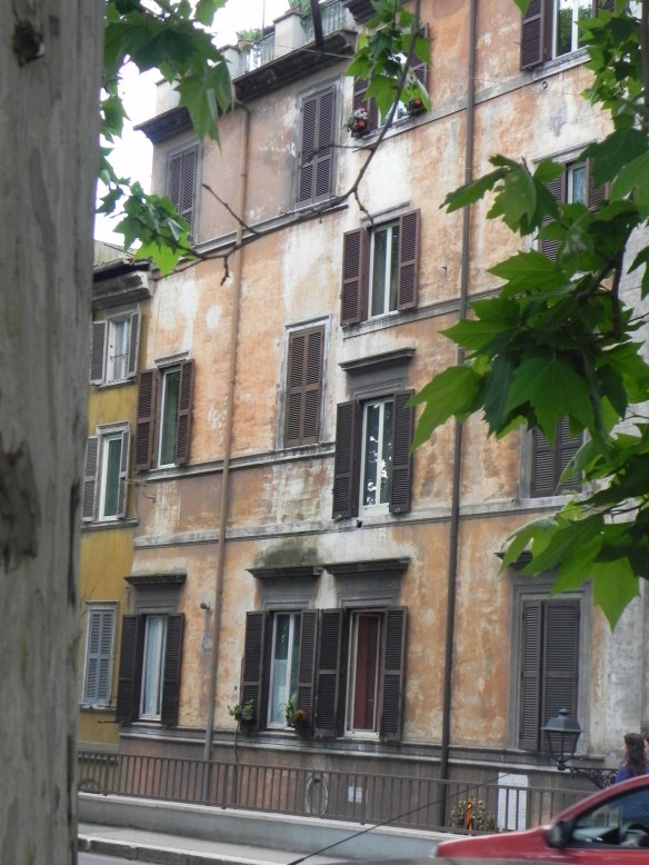 photo of the architecture of a building by the river with its orange vintage paint and retro windows in rome