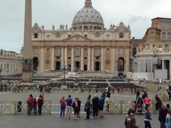 st peters Basilica square at the vatican city with people waiting in lone and the cross is apparent beautiful architecture
