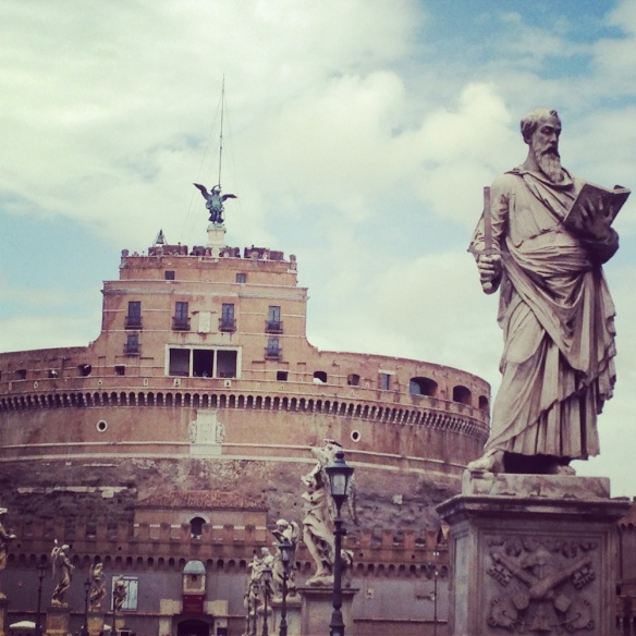 a beautiful natural brown photo of castel saint'angelo and the statue infront of the gate