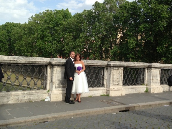 a wedding at the castel saint'angelo bride and groom being photographed nearby the bridge