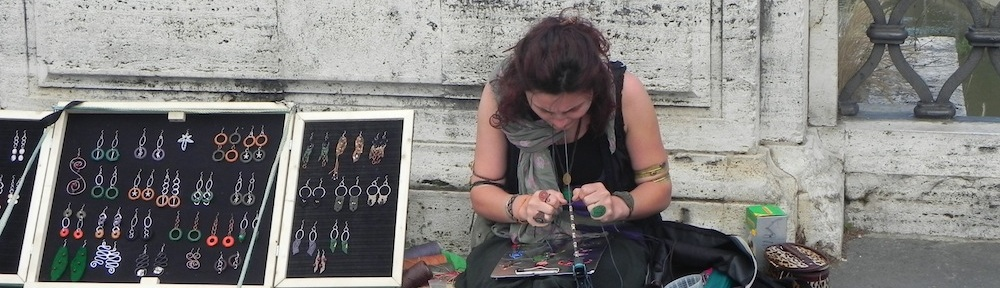 a hippie artists working with threads to create bracelets to sell to tourists at the castel st angelo