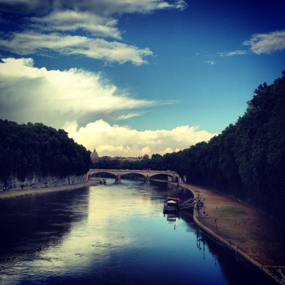 one of my favorite photos of rome with blue blue skies reflection on the blue river and the green long trees on the side travelblog