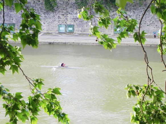 a photo of a man canoeing alone in the middle of the river tevere in rome