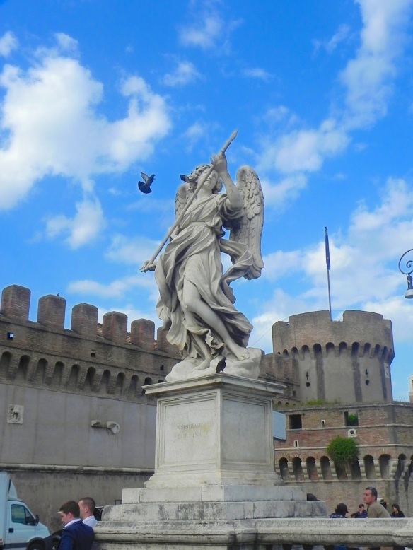 one of the st angelo statue looking as if it is targeting a bird that is truly flying the blue skies