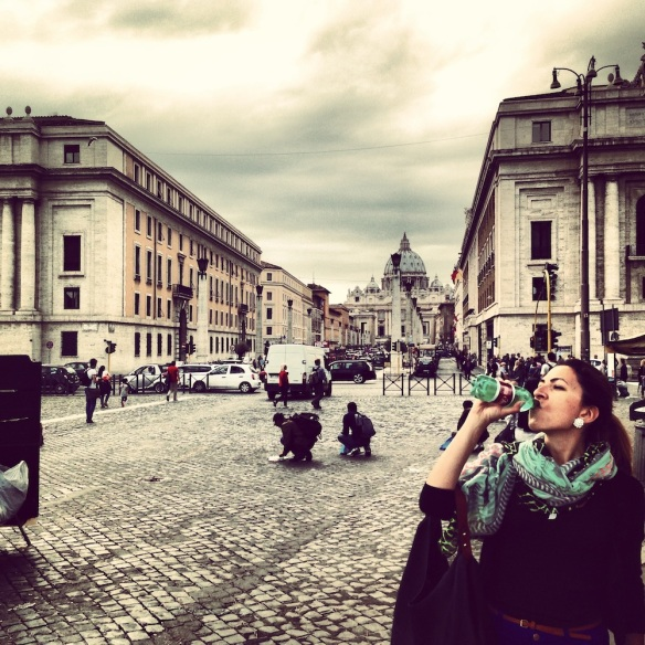 after a long walk i am drinking water from thirst in the streets of the vatican city rome