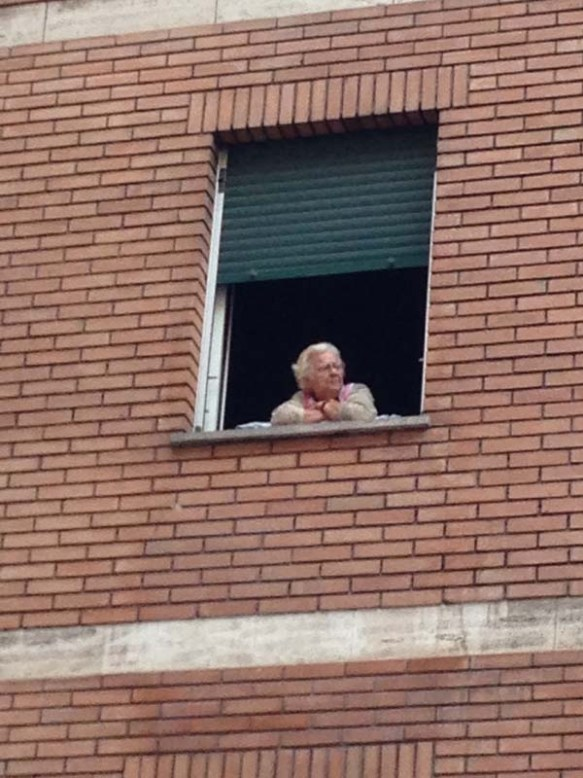 An old woman is looking out from her homes window of a brick building