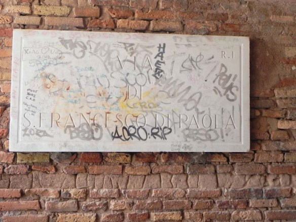 Street sign that is covered with graffiti in rome