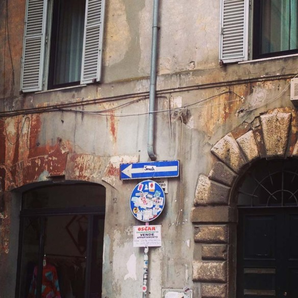 A very humble street sign in rome with an arrow pointing to the left
