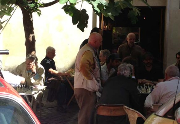 old men playing chess outdoors of the bar del fico