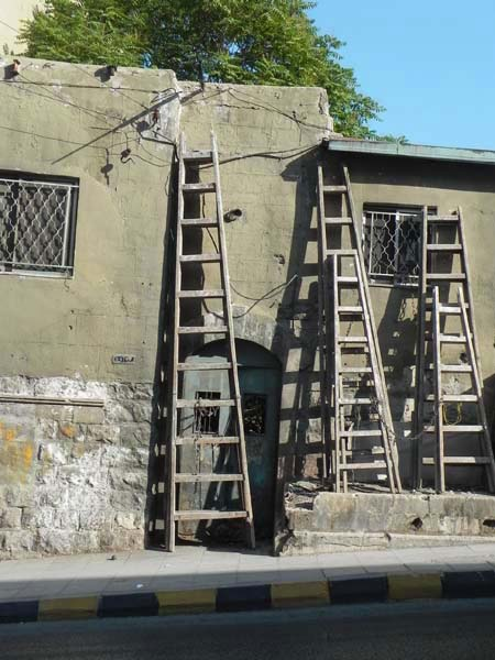 three ladders of all sized leaning on antique vintafe buildings downtown amman