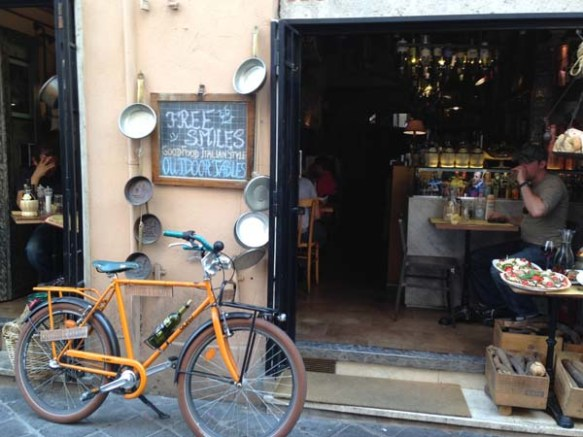 a retro vintage hip looking bicycle lying on a wall next to a shop at the campo de'fiori