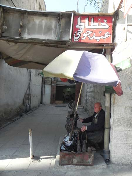 An old man still making shoes and asking for money at albalad downtown Amman