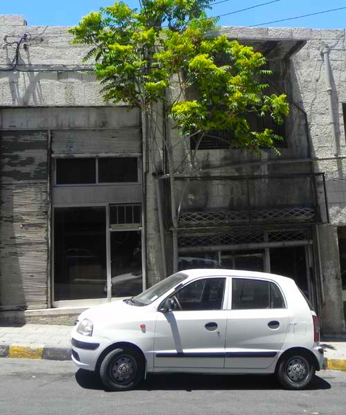 A white car parked infront of a very old house on the way to downtown amman al balad