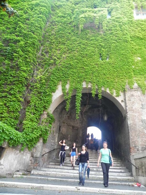 A bridge with green trees all over and tourists walking underneath rome