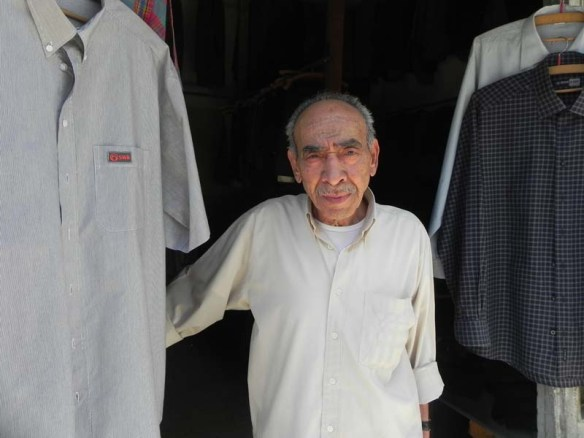 Portrair of An old man still working at his own menswear shop downtown albalad