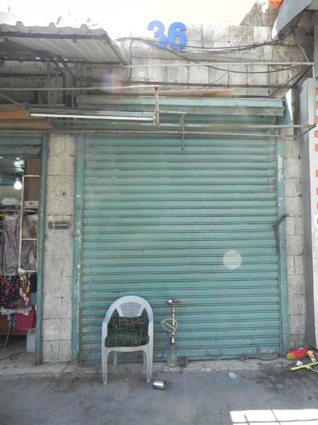 A closed green garage door with a shisha argeeleh or hubblly bubbly and an empty chair infront of it albalad amman