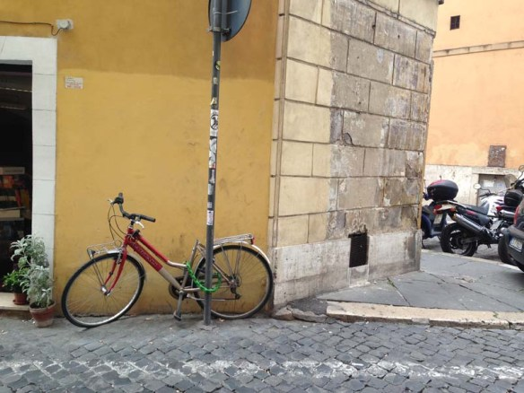 A beautiful yellow mustard wall with a bicycle leaning on it in rome