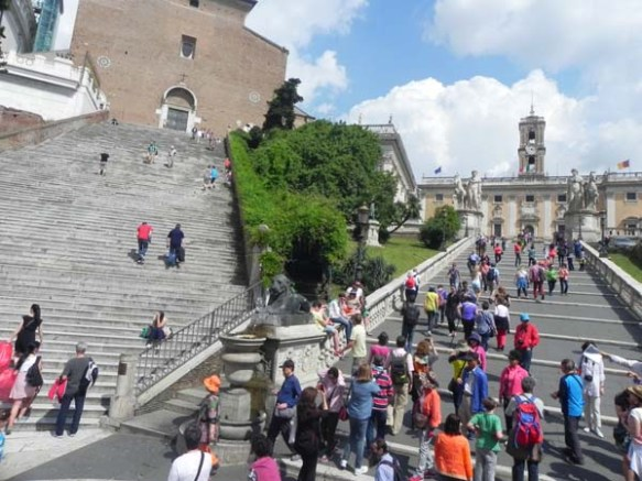 people and tourists climbing the Capitoline Hill in rome italy