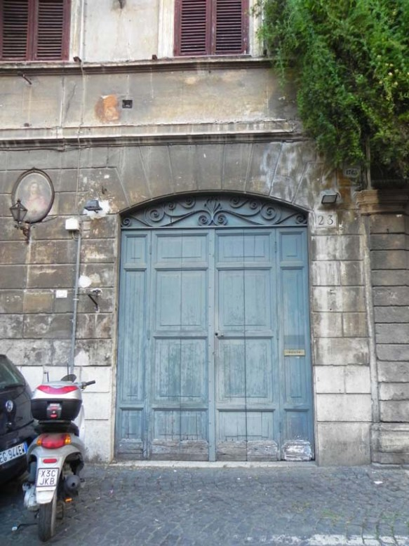A very big garage or door with a motorbike parking right infront of it Rome