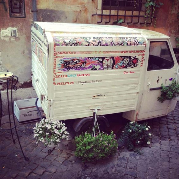 a small white bus carrying plants and flowers as an art piece in the streets on navona rome