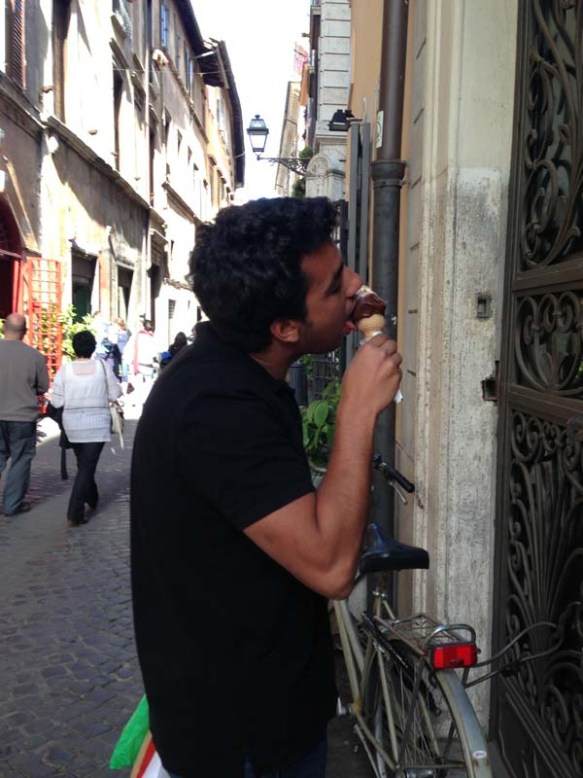 a guy licking icecream infront of a gelateria