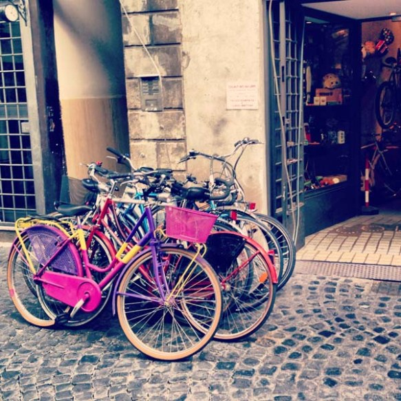 multiple colored bikes on the entrance of a bike shop