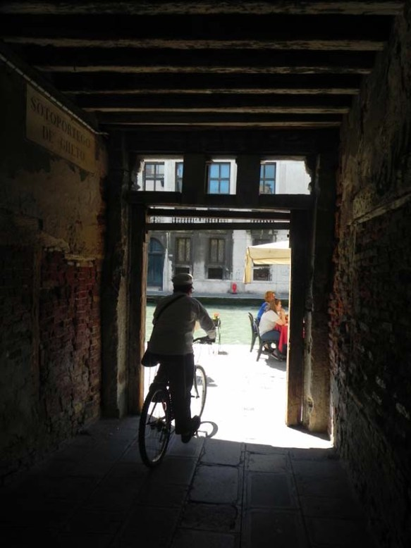 An old man biking outside a door in the ghetto area with the shadow behind him and the light infront of him at Venice Venezia