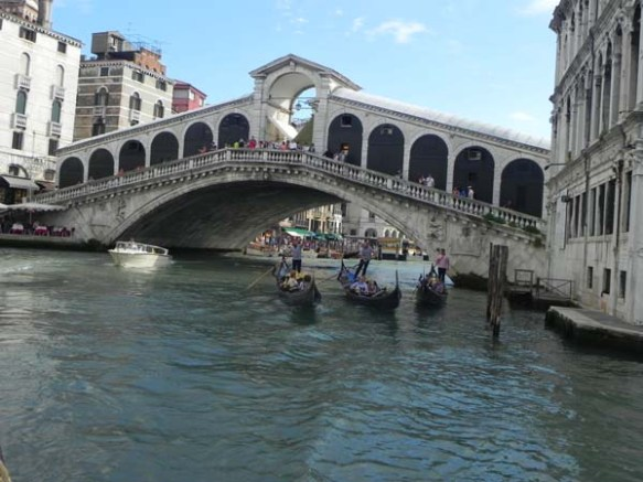 A gondola and a gondolier at the Grand Canal under bridge venice venezia