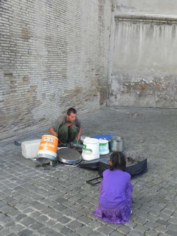 A hippie playing drums in the middle of the street with little girl watching