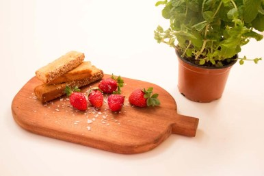 Strawberries in a wood mat and some green plants