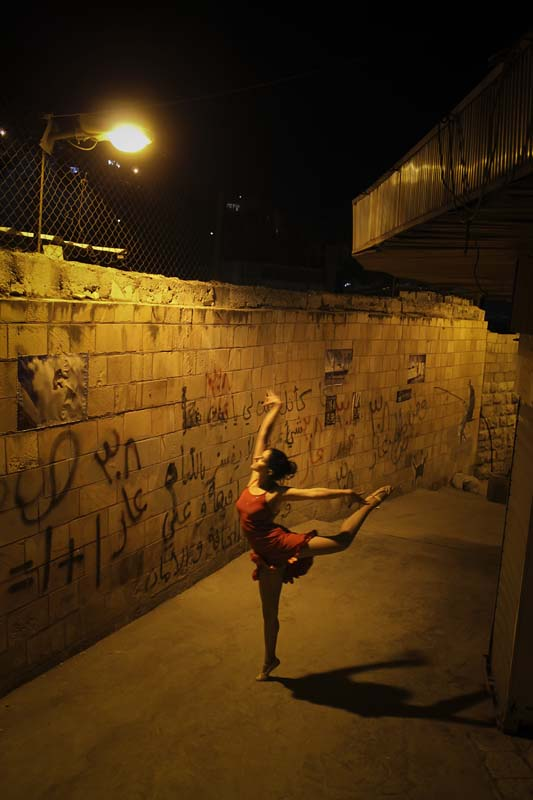 A balet dancer in a ghetto area under yellow light webdeh amman jordan