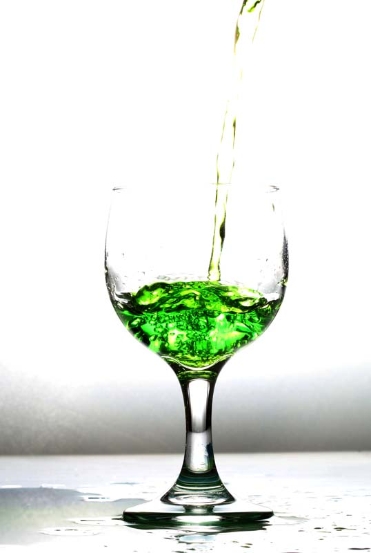 A picture of a glass being filled with green water liquid