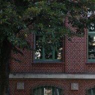 Red brick building with green windows and tree in berlin