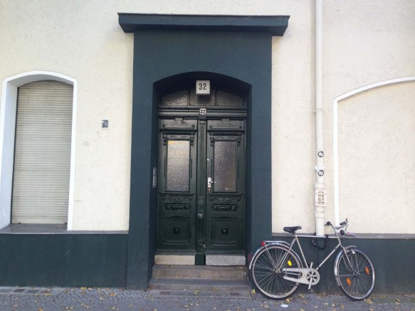 Bicycle with a beige and blue door wall in berlin