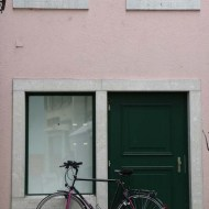 Bicycle parked at green door and pink wall in solothurn