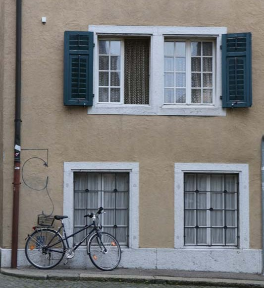 Bike parked at a beige building and green fenetre in solothurn switzerland