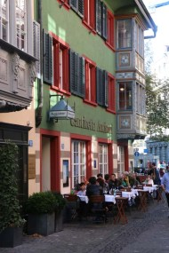 A photograph of green and red old building in Zurich Altstadt old town first district