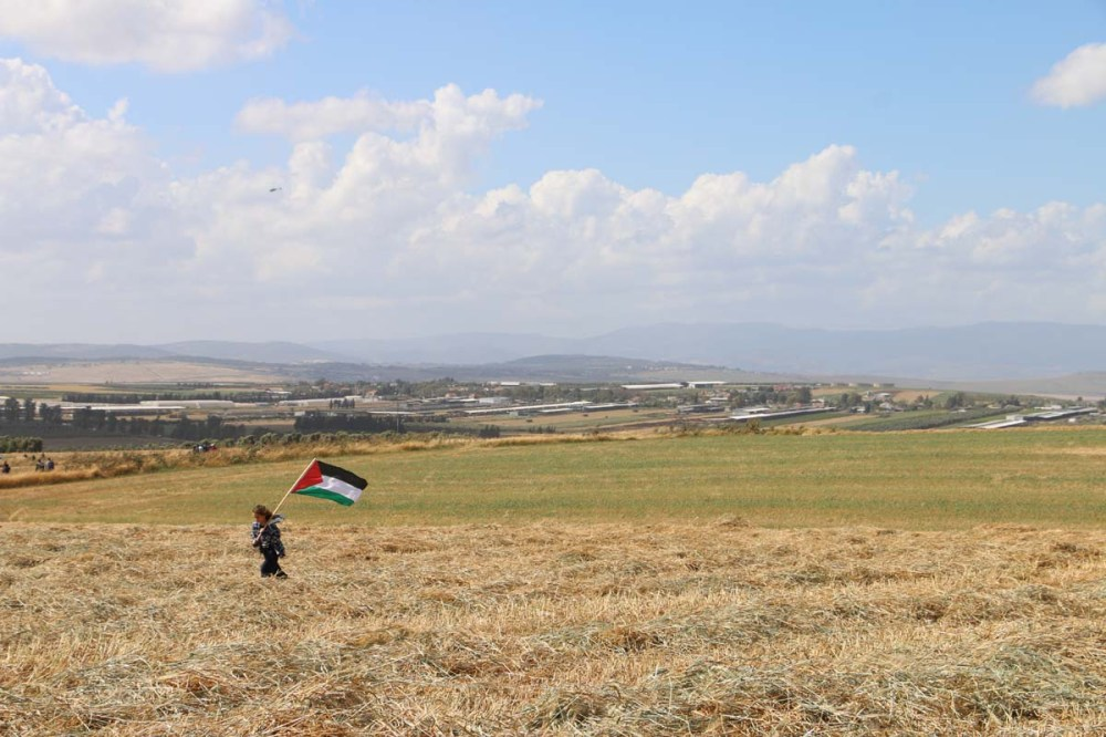 Palestine flag while a kid is carrying it over hay